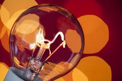 Lit electrical light bulb with warm red background royalty free stock images