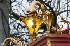 A lit forged street lamp with two lamps and round glare of light.  Royalty Free Stock Images