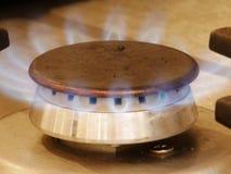 Lit Gas Burner on Hob. Lit gas burner on stainless steel hob with blue flames stock image