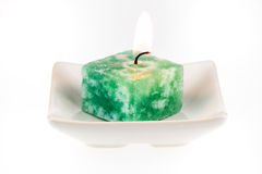 Lit green candle on a plate Stock Images