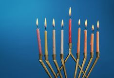 The lit of hanukkah candles in menorah on blue background. The lit of hanukkah candles in a menorah on blue background royalty free stock photo