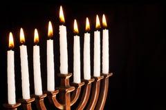 Lit hanukkah menorah black background. Stock Photos