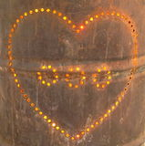 Lit heart. Lit up heart on metallic barrel pierced with holes Royalty Free Stock Photography