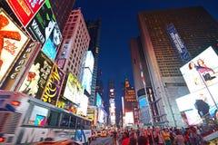 Lit herauf New York Time Square am Abend mit einem Bus, der vorbei überschreiten und crowdq Lizenzfreies Stockfoto