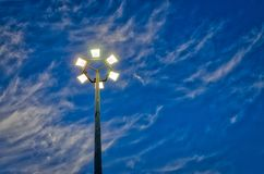 Lit hexagonal streetlight under dramatic sky. Six streetlights in a hexagonal pattern under a blue sky with dramatic clouds. Powered on for the evening Stock Image