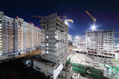 Lit high multi-storey buildings under construction Stock Photos