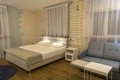 Lit intérieur et double de chambre à coucher, sofa et grandes fenêtres photographie stock