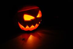 Lit Jack O Lantern pumpkin. Close up of Jack O Lantern Halloween pumpkin face with spiders in eyes Royalty Free Stock Photography