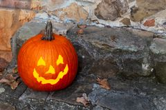A lit jack-o-lantern welcoming children to a home for trick-or-treating on Halloween. stock photos