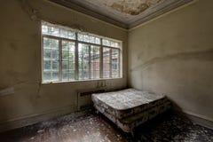 Lit jumeau avec la fenêtre et les planchers en bois dur - manoir abandonné Images stock
