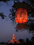Lit Lantern and Glowing Statue. A Lantern dangles from a tree at the Toronto Chinese Lantern Festival royalty free stock photos