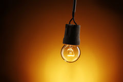 A lit light bulb. On yellow background Stock Photos