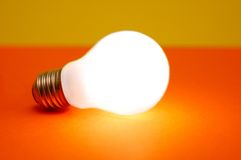 Lit light bulb. Lit bulb on orange and yellow background, conceptual photo Royalty Free Stock Image