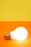 Lit light bulb. Lit bulb on orange and yellow background Royalty Free Stock Images