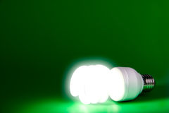 A lit light bulb. On a green background Royalty Free Stock Images