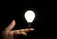 Lit light bulb balancing on finger Stock Photography