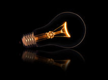 Lit light bulb on black background Stock Photography