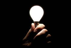 Lit lightbulb held in hand on black background Stock Photos