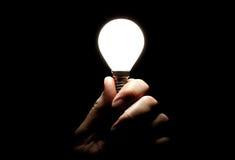 Lit lightbulb held in hand on black background. Lit lightbulb held up by a hand gripping the screw base, on a blackbackground Stock Photos
