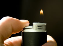 Lit lighter. Against black background Royalty Free Stock Photos