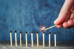 A lit match in hand tries to set another match on fire. The conc Stock Photography