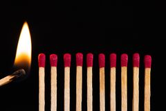 Lit match next to a row of unlit matches. stock photography