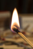 Lit Match. A lit match with a stack of unlit matches in the background Royalty Free Stock Images