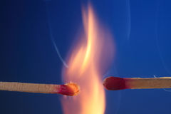 Lit matchstick next to an unlit matchstick Stock Photo