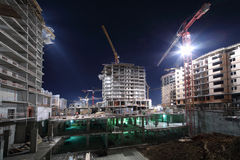 Lit multi-storey buildings under twenty-four-hour construction Stock Photo
