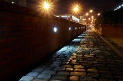 Lit- och kullerstengränd på natten Royaltyfria Bilder