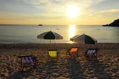 Lit pliant et parapluie au rivage sur le fond de coucher du soleil photo stock