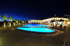 Lit pool area of a resort at night Royalty Free Stock Image