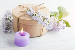 Lit purple candle and lilac flowers Royalty Free Stock Photo