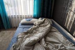Lit qui n'est pas encore fait dans la chambre à coucher pendant le matin Image libre de droits