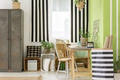Lit rayé à côté de chaise en bois au bureau dans l'inte vert d'espace de travail Image stock