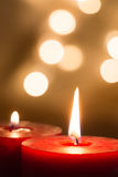 Lit red candles closeup and golden background Royalty Free Stock Photos