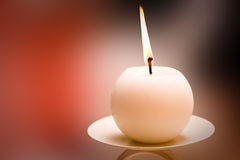 Lit Round Candle. With a colourful background Stock Image