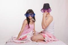 Lit se reposant de jeunes couples avec de grands verres, type dans le chapeau Photographie stock libre de droits