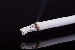 Lit single cigarette with smoke  on black background Royalty Free Stock Photos