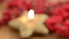 Lit of star shape Christmas candle. Aside sweets like cinnamon pastry and red pearl.  stock video footage
