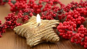 Lit of star shape Christmas candle. Aside sweets like cinnamon pastry and red pearl.  stock video