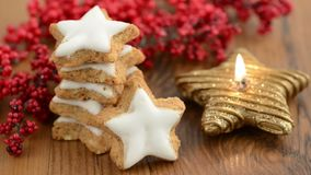 Lit of star shape Christmas candle. Aside sweets like cinnamon pastry and red pearl.  stock footage