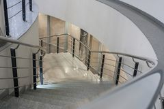 Lit stone spiral staircase with metal railing. Stock Photos