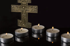Lit Tea Candles with Crucifix with dark Background. Lit Tea Candles and reflections with Crucifix with dark Background Stock Images