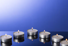 Lit Tea Candles with Reflection on Blue. Background Royalty Free Stock Images