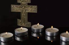 Lit-Tee-Kerzen mit Kruzifix mit dunklem Hintergrund stockbilder