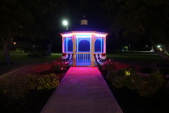 A lit up gazebo with flags of red white and blue Stock Photography