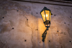 Lit up street lamp in Prague on the side of a nice patterned wall Royalty Free Stock Photo