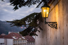 Lit up street lamp in Prague on the side of a nice patterned wall Stock Images