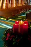 Lit-Weihnachtskerzen und -Wreath in der leeren Kirche Stockfotografie
